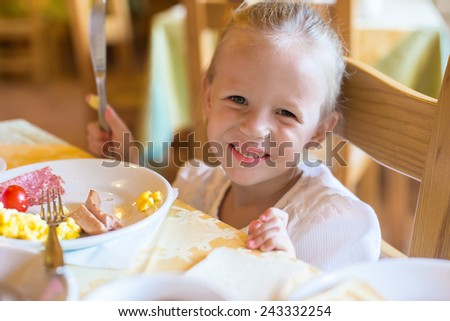 Adorable little girl having breakfast at indoor cafe - stock photo