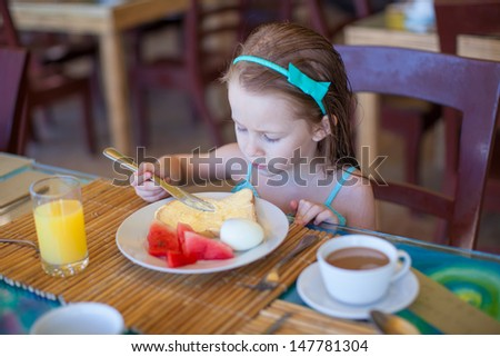 Adorable little girl having breakfast at resort restaurant - stock photo