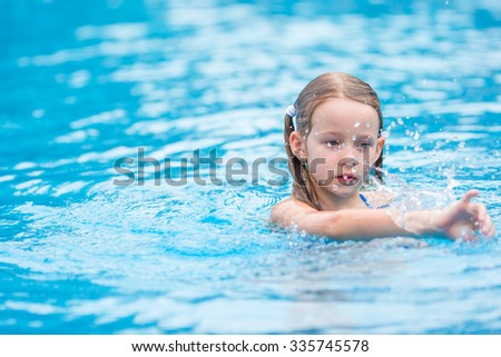 Adorable little girl having fun in outdoor swimming pool