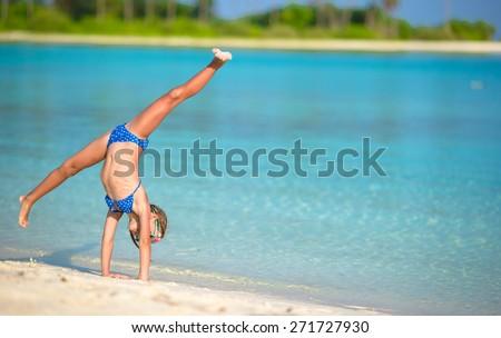 Adorable little girl having fun making cartwheel on tropical white sandy beach - stock photo
