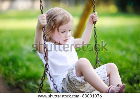 Adorable little girl having fun on a swing - stock photo
