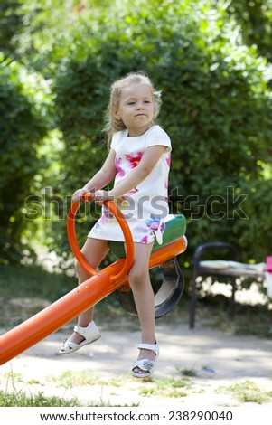 Adorable little girl having fun on a swing, against background of summer park - stock photo