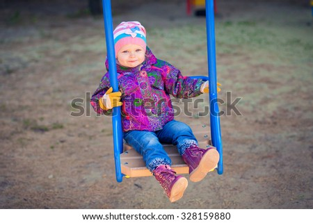 Adorable little girl having fun on a swing outdoor . Child, Playing, Playground. joyful autumn cheerful playground. - stock photo
