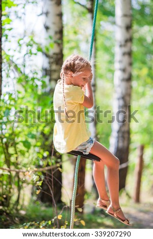 Adorable little girl having fun on a swing outdoors - stock photo