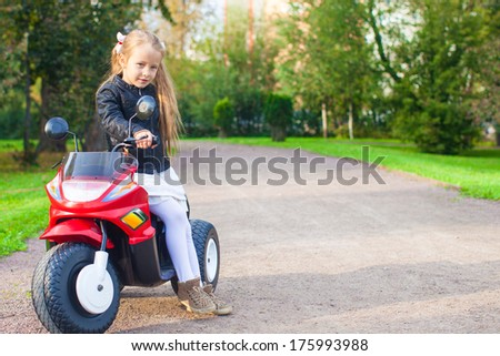 Adorable little girl having fun on her toy motorcycle - stock photo