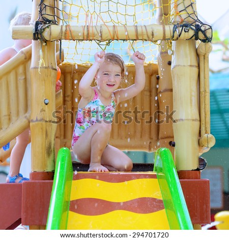 Adorable little girl having fun on waterslide in recreational swimming pool. Happy toddler kid enjoying day in aqua park. - stock photo