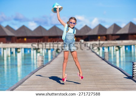 Adorable little girl having fun on wooden jetty near water bungalow - stock photo