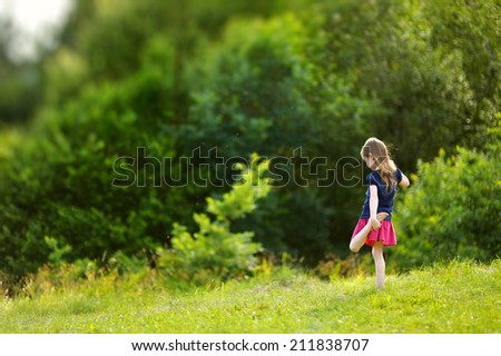 Adorable little girl having fun outdoors on beautiful summer day