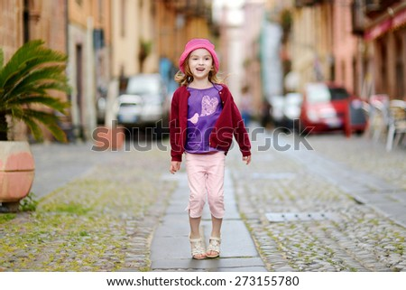 Adorable little girl having fun outdoors on hot summer day - stock photo
