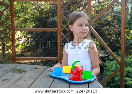 Adorable little girl, having fun playing with toy kitchen outdoors in the garden at the backyard of the house on a sunny summer day