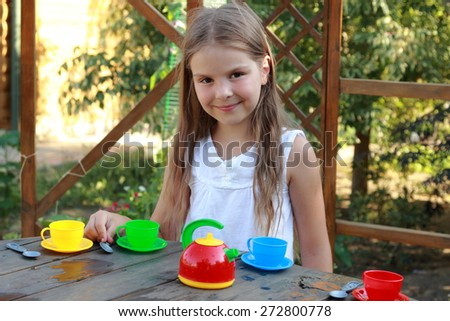 Adorable little girl, having fun playing with toy kitchen outdoors in the garden at the backyard of the house on a sunny summer day - stock photo