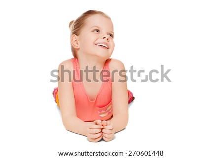 Adorable little girl having fun smiling is lying looking to the side, isolated on white background - stock photo