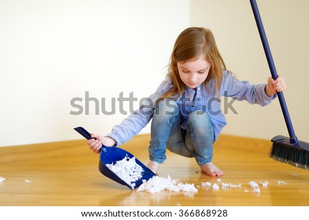 Adorable little girl helping her mom to clean up at home - stock photo