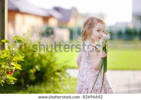 Adorable little girl helping in a garden - stock photo