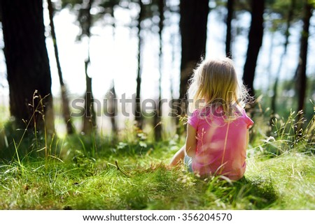 Adorable little girl hiking in the forest on summer day - stock photo