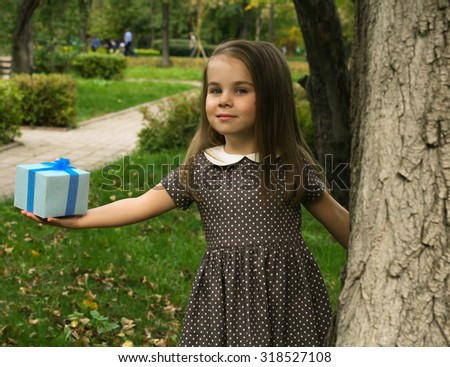 Adorable little girl hold blue gift box in park - stock photo