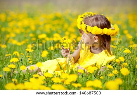 Adorable little girl holding a bouquet of flowers - stock photo