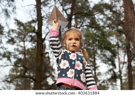 Adorable little girl holding a paper plane in the forest, outdoors on sunny spring day - stock photo