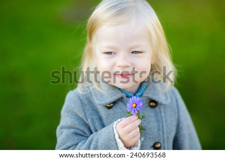 Adorable little girl holding a purple flower - stock photo