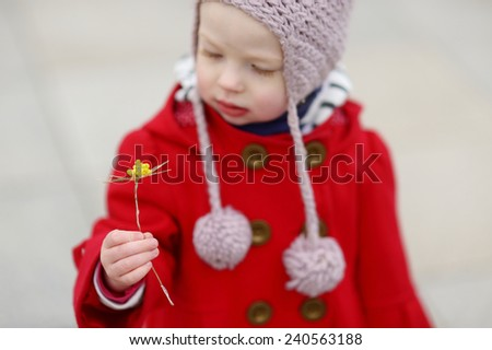 Adorable little girl holding straw flower as part of Easter tradition in Lithuania - stock photo