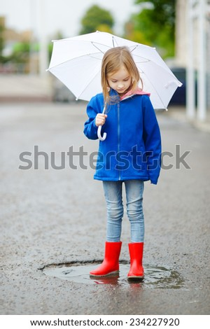Adorable little girl holding white umbrella standing in a puddle on warm autumn day - stock photo