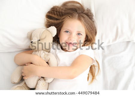 Adorable little girl hugging teddy bear in bed
