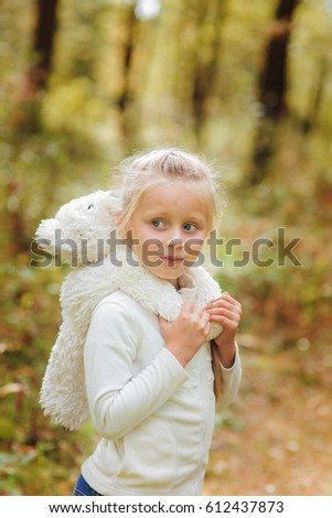 Adorable little girl hugs her favorite soft toy in a summer day in the park