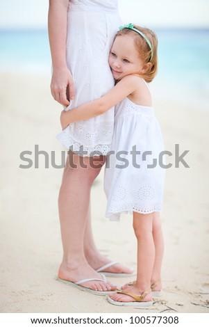 Adorable little girl hugs her mom at beach - stock photo