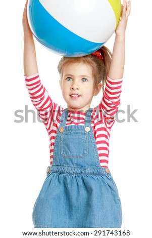 Adorable little girl in a blue dress holding over his head a large beach ball - isolated on white background - stock photo