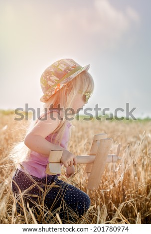 Adorable little girl in a colorful sunhat and sunglasses playing outdoors in a summer wheat field with a wooden model of a vintage biplane - stock photo