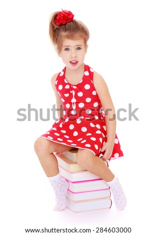 Adorable little girl in a red dress with polka dots sitting on a stack of books- isolated on white background - stock photo