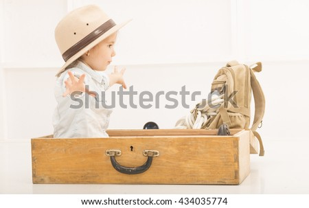Adorable little girl in a safari hat and explorer clothes flying an old suitcase. Children's play concept - stock photo