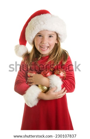 Adorable Little Girl in a Santa Hat and Red Velvet Dress For Christmas.  She is holding an armful of Christmas ornaments