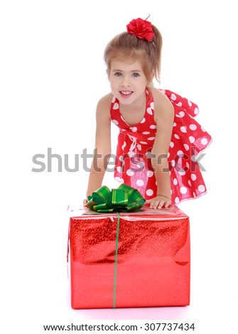 Adorable little girl in a short summer dress with polka dots, bent over to examine a large beautifully packaged box tied with a bow.In the box is a gift that she has received my parents for my - stock photo