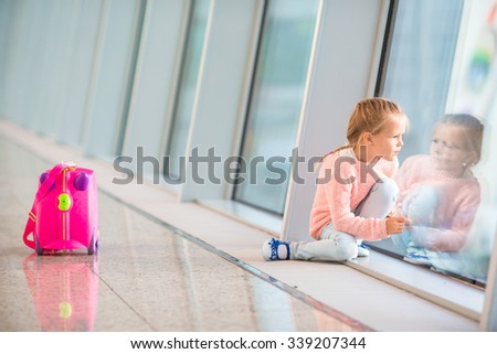 Adorable little girl in airport with her luggage waiting for boarding - stock photo