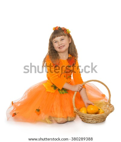 Adorable little girl in an orange dress with orange vegetables - Isolated on white background - stock photo