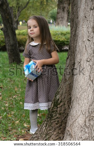 Adorable little girl in beautiful dress with blue gift box - stock photo
