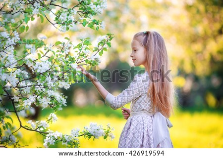 Adorable little girl in blooming apple tree garden on spring day - stock photo