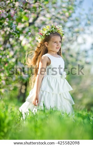 Adorable little girl in blooming  garden on beautiful spring day - stock photo