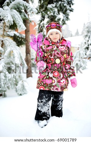 Adorable little girl in colorful snow suit and hat with fairy wing and magic wand plays outside in snowfall