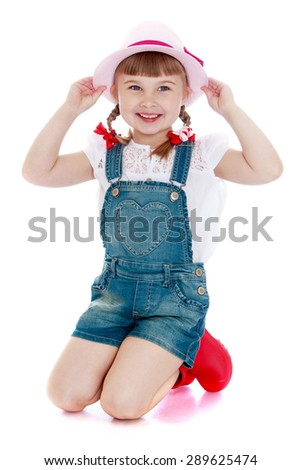 Adorable little girl in denim overalls and a hat - isolated on white background - stock photo