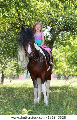 Adorable little girl in dress galloping on her horse