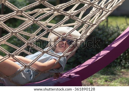 Adorable little girl in hammock enjoying the sun - stock photo