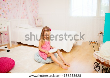 Adorable little girl in her room reading - stock photo