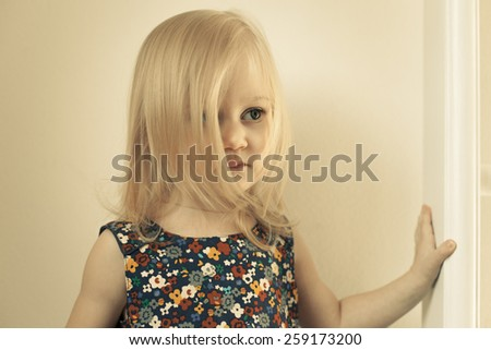Adorable little girl in her room. Thoughtful, pensive face. The face is covered with long hair - stock photo