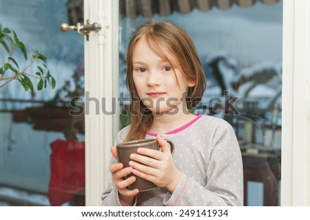 Adorable little girl in pajamas drinking her morning hot chocolate by the window