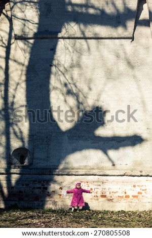 Adorable little girl in pink coat staying near the wall. Unusual tree shadows contrasts with little girl. Color and size contrast. - stock photo