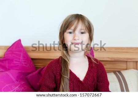 Adorable little girl in pullover in parent's bed