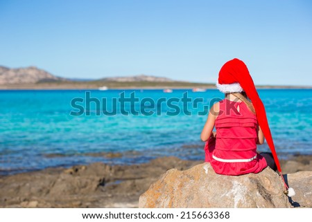 Adorable little girl in Santa hat and red dress sitting on big stone