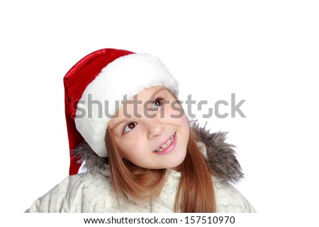 adorable little girl in Santa's hat looking up isolated on white